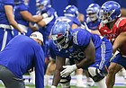 Kansas offensive line coach Luke Meadows gets down as he works with lineman Hakeem Adeniji as he snaps to quarterback Miles Kendrick on Thursday, April 4, 2019 at the indoor practice facility.