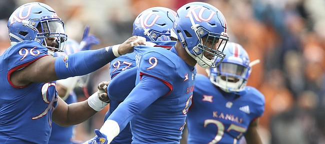 Kansas defensive end Najee Stevens-McKenzie (9) celebrates an interception during the second quarter with Kansas defensive tackle Daniel Wise (96) and others on Friday, Nov. 23, 2018 at Memorial Stadium.