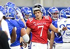 Kansas quarterback Thomas MacVittie high fives his teammates after breaking from a team huddle during practice on Thursday, Aug. 8, 2019.
