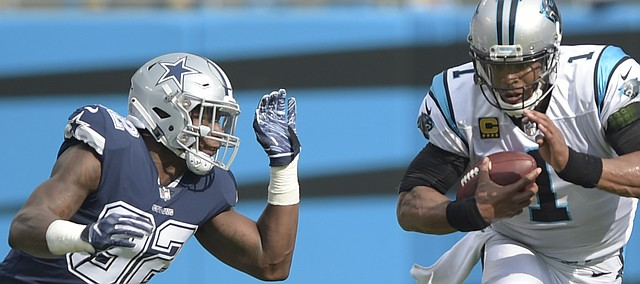 Carolina Panthers' Cam Newton (1) scrambles past Dallas Cowboys' Dorance Armstrong (92) during the first half of an NFL football game in Charlotte, N.C., Sunday, Sept. 9, 2018. (AP Photo/Mike McCarn)