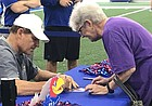 Kansas football coach Les Miles signs an autograph for Vicky Mall, of Clay Center, on Saturday, Aug. 10, 2019, during the team's Fan Day, at the indoor practice facility.