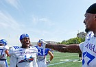 Kansas safety Mike Lee, center, and cornerback Elijah Jones have a laugh during a break from practice on Friday, Aug. 9, 2019.