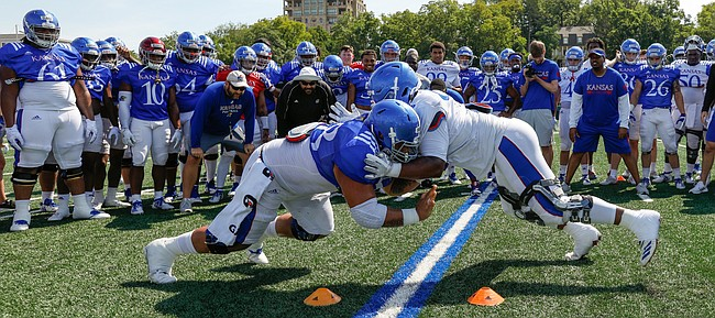 Kansas center Api Mane, left, and defensive tackle Jelani Brown go head-to-head in the Jayhawk drill during practice on Friday, Aug. 9, 2019.