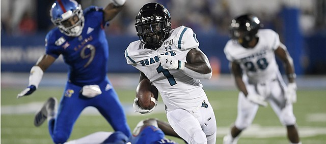 Coastal Carolina's CJ Marable gets past two Kansas defenders Saturday night at David Booth Kansas Memorial Stadium on Sept. 7, 2019.