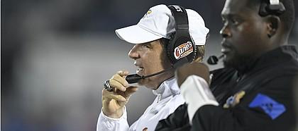Kansas head coach Les Miles talks on the radio to assistants Saturday against Coastal Carolina Saturday night at David Booth Kansas Memorial Stadium on Sept. 7, 2019.