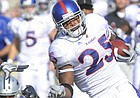 Kansas kick returner Darrell Stuckey (25) takes the ball up the sideline with KSU's Lamark Brown (7) in pursuit against Kansas State in Manhattan Saturday, November 7, 2009.