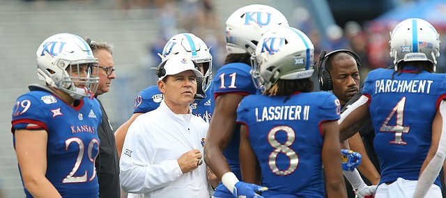 Kansas head coach Les Miles heads into the huddle with his team during the third quarter on Saturday, Sept. 21, 2019 at David Booth Kansas Memorial Stadium.