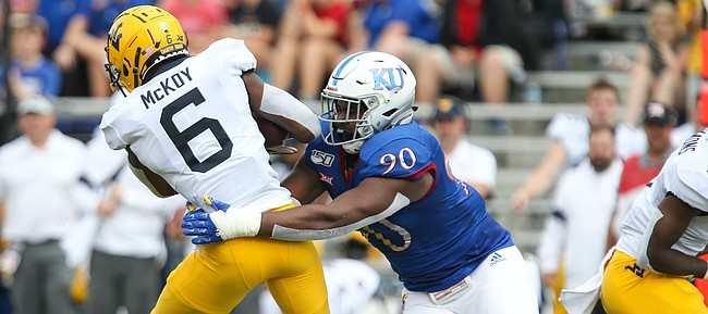 Kansas defensive tackle Jelani Brown (90) brings down West Virginia running back Kennedy McKoy (6) for a loss during the first quarter on Saturday, Sept. 21, 2019 at David Booth Kansas Memorial Stadium.