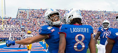 Kansas wide receiver Stephon Robinson Jr. (5) left, and Kansas running back Khalil Herbert (10) come in to celebrate with Kansas wide receiver Kwamie Lassiter II (8) after Lassiter's touchdown during the second quarter on Saturday, Sept. 21, 2019 at David Booth Kansas Memorial Stadium.