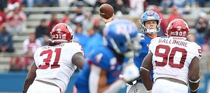 Kansas quarterback Carter Stanley (9) throws as Oklahoma linebacker Jalen Redmond (31) and Oklahoma defensive lineman Neville Gallimore (90) close in during the third quarter on Saturday, Oct. 5, 2019 at Memorial Stadium.