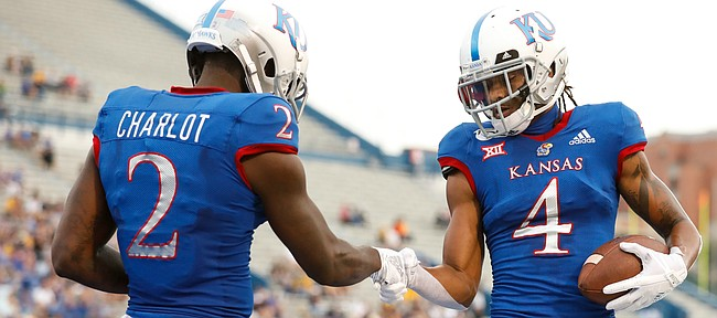 Kansas wide receiver Andrew Parchment (4) and Kansas wide receiver Daylon Charlot (2) celebrate Parchment's fourth-quarter touchdown with a handshake on Saturday, Sept. 21, 2019 at David Booth Kansas Memorial Stadium.
