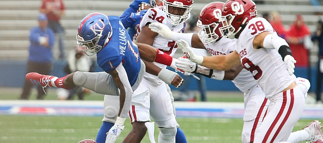 Kansas running back Pooka Williams Jr. (1) gets taken off his feet by the Oklahoma defense on a run in the first quarter on Saturday, Oct. 5, 2019 at Memorial Stadium.