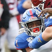 Kansas running back Pooka Williams Jr. (1) is put on the turf by the Oklahoma defense on a run in the first quarter on Saturday, Oct. 5, 2019 at Memorial Stadium.
