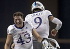 Kansas quarterback Carter Stanley (9) celebrates a touchdown against Texas with linebacker Jay Dineen (43) during an NCAA college football game Saturday, Oct. 19, 2019, in Austin, Texas. (Nick Wagner/Austin American-Statesman via AP)