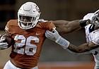 Texas running back Keaontay Ingram (26) stiff-arms Kansas cornerback Hasan Defense (13) during an NCAA college football game Saturday, Oct. 19, 2019, in Austin, Texas. (Nick Wagner/Austin American-Statesman via AP)