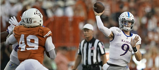 Kansas' Carter Stanley (9) looks to pass under pressure from Texas' Ta'Quon Graham (49) during the first half of an NCAA college football game in Austin, Texas, Saturday, Oct. 19, 2019. (AP Photo/Chuck Burton)
