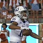 Kansas' Takulve Williams (16) celebrates his touchdown as Texas' Anthony Cook (4) and Kansas' Daylon Charlot (2) look on during the first half of an NCAA college football game in Austin, Texas, Saturday, Oct. 19, 2019. (AP Photo/Chuck Burton)