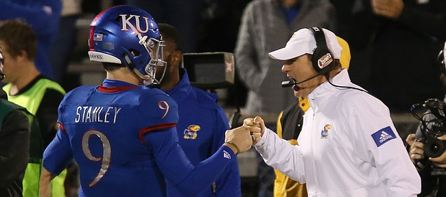 Kansas football Les Miles, right, greets Carter Stanley (9) after Stanley threw for a touchdown in the second half of KU's 37-34 win against Texas Tech.