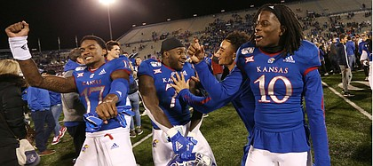 The Kansas football team celebrates following a 37-34 win over Texas Tech Saturday night at David Booth Kansas Memorial Stadium on Oct. 26, 2019.