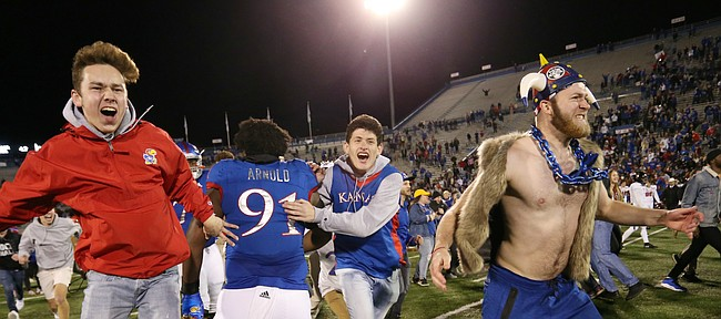 Fans charge the field and congratulate players after KU defeated Texas Tech 37-34 Saturday at Memorial Stadium.