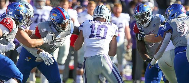 Kansas State quarterback Skylar Thompson (10) squeezes between Kansas defensive end Darrius Moragne (97) and Kansas linebacker Azur Kamara (5) during the first quarter on Saturday, Nov. 2, 2019 at Memorial Stadium.