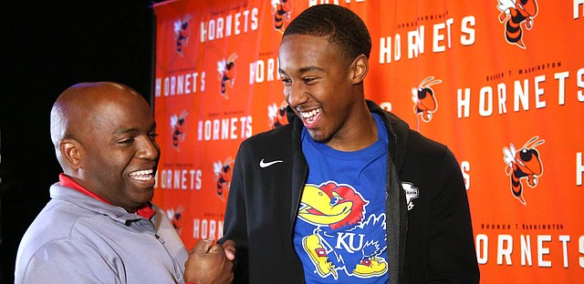 Booker T. Washington basketball player Bryce Thompson, right, celebrates with former coach Joe Redmond after announcing his signing with the University of Kansas in Tulsa, Okla., on Tuesday, November 12, 2019.