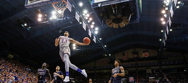 Kansas guard Tristan Enaruna (13) soars in for a breakaway dunk against Monmouth during the second half on Friday, Nov. 15, 2019 at Allen Fieldhouse.