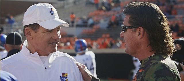 Kansas head coach Les Miles, left, talks with Oklahoma State head coach Mike Gundy, right, before an NCAA college football game in Stillwater, Okla., Saturday, Nov. 16, 2019. (AP Photo/Sue Ogrocki)