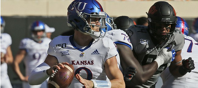 Kansas quarterback Carter Stanley (9) passes in the first half of an NCAA college football game against Oklahoma State in Stillwater, Okla., Saturday, Nov. 16, 2019. (AP Photo/Sue Ogrocki)