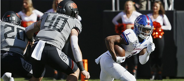 Kansas running back Pooka Williams Jr. (1) carries past Oklahoma State defensive end Brock Martin (40) in the first half of an NCAA college football game in Stillwater, Okla., Saturday, Nov. 16, 2019. (AP Photo/Sue Ogrocki)