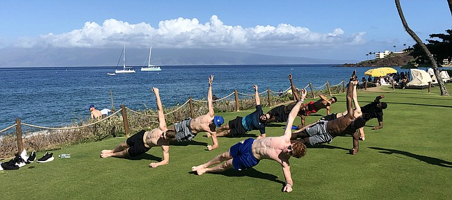 Jayhawks Michael Jankovich, Mitch Lightfoot, Ochai Agbaji, Devon Dotson, Isaiah Moss, Elijah Elliott, Silvio De Sousa and Chris Teahan hold a side plank during a morning workout with new strength and conditioning coach Ramsey Nijem near the beach outside of their resort in Maui on Sunday, Nov. 24, 2019.