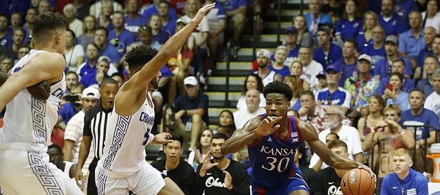 Kansas guard Ochai Agbaji (30) dribbles through the Chaminade defense during an NCAA college basketball game Monday, Nov. 25, 2019, in Lahaina, Hawaii. (AP Photo/Marco Garcia)