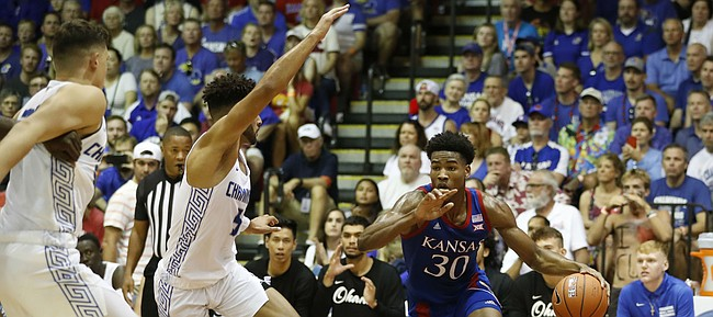 Kansas guard Ochai Agbaji (30) dribbles through the Chaminade defense during an NCAA college basketball game Monday, Nov. 25, 2019, in Lahaina, Hawaii. (AP Photo/Marco Garcia)
