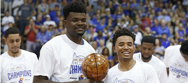 Kansas center Udoka Azubuike, left, and guard Devon Dotson share the Maui Invitational co-MVP trophy, Wednesday, Nov. 27, 2019, in Lahaina, Hawaii. Kansas defeated Dayton in 90-84 in overtime in an NCAA college basketball game for the tournament title. (AP Photo/Marco Garcia)
