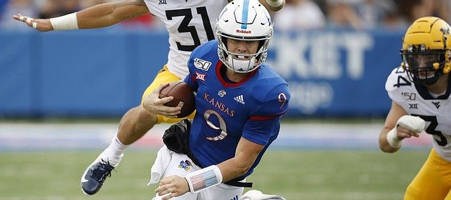 Kansas quarterback Carter Stanley (9) scrambles for a first down as he slips past West Virginia safety Jovanni Stewart (9) linebacker Zach Sandwisch (31) and linebacker Shea Campbell (34) during an NCAA football game on Saturday, Sept. 21, 2019 in Lawrence, Kan. (AP Photo/Colin E. Braley)