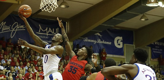 Kansas guard Marcus Garrett (0) goes to the net over Dayton guard Dwayne Cohill (35) during the first half of an NCAA college basketball game Wednesday, Nov. 27, 2019, in Lahaina, Hawaii. (AP Photo/Marco Garcia)