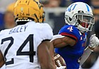 Kansas wide receiver Andrew Parchment (4) runs past West Virginia cornerback Hakeem Bailey (24) on his way to a touchdown during the second half of an NCAA college football game in Lawrence, Kan., Saturday, Sept. 21, 2019. (AP Photo/Orlin Wagner)