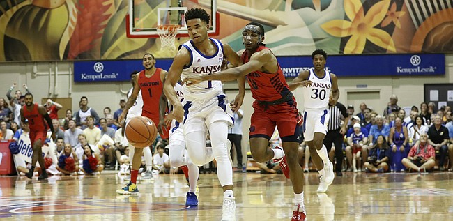 Kansas guard Devon Dotson (1) and Dayton guard Rodney Chatman (0) chase down a loose ball during the first half of an NCAA college basketball game Wednesday, Nov. 27, 2019, in Lahaina, Hawaii. (AP Photo/Marco Garcia)