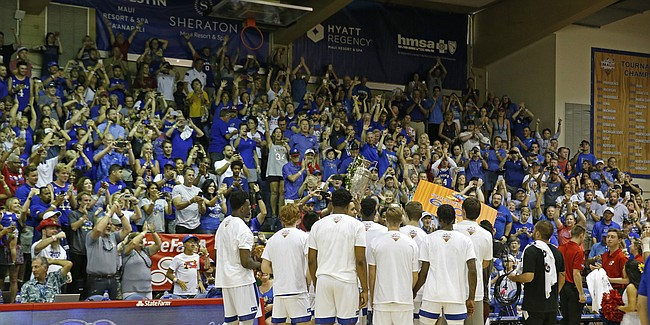 While holding the winning trophy, Kansas celebrates with their fans after defeating Dayton 90-84 in overtime in an NCAA college basketball game Wednesday, Nov. 27, 2019, in Lahaina, Hawaii. (AP Photo/Marco Garcia)