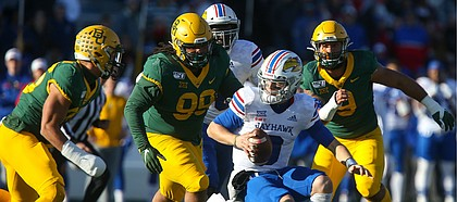 Three Baylor defenders close in on Kansas quarterback Carter Stanley (9) during the first quarter on Saturday, Nov. 30, 2019 at Memorial Stadium.