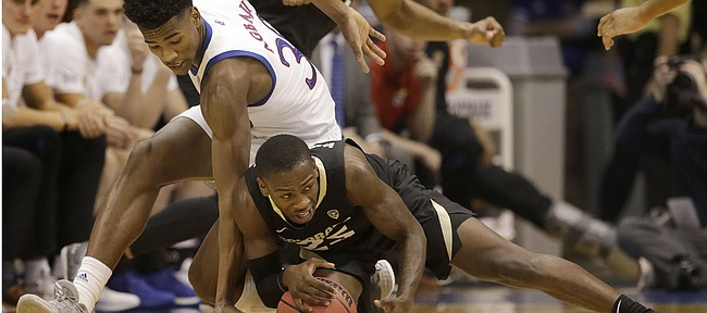 Kansas' Ochai Agbaji, left, and Colorado's McKinley Wright IV chase the ball during the first half of an NCAA college basketball game Saturday, Dec. 7, 2019, in Lawrence, Kan. (AP Photo/Charlie Riedel)