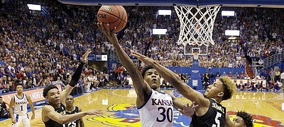Kansas' Ochai Agbaji (30) gets past D'Shawn Schwartz (5) to shoot during the first half of an NCAA college basketball game Saturday, Dec. 7, 2019, in Lawrence, Kan. Kansas won 72-58. (AP Photo/Charlie Riedel)