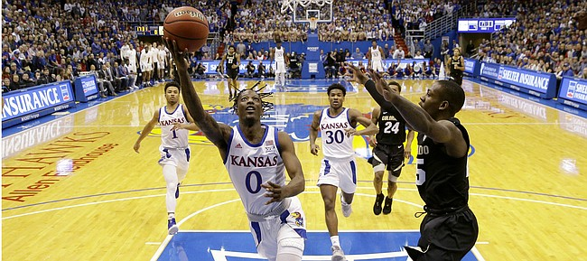 Kansas' Marcus Garrett (0) gets past Colorado's McKinley Wright IV, right, to shoot during the first half of an NCAA college basketball game Saturday, Dec. 7, 2019, in Lawrence, Kan. (AP Photo/Charlie Riedel)