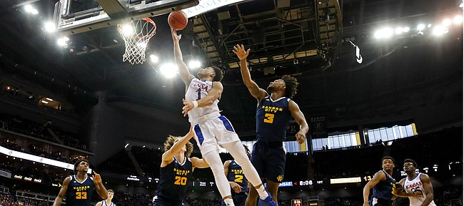 Kansas guard Devon Dotson (1) gets inside for a bucket past UMKC guard Brandon McKissic (3) during the first half, Saturday, Dec. 14, 2019 at Sprint Center in Kansas City, Mo.
