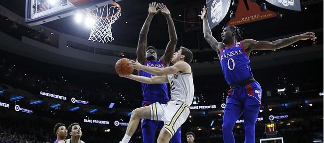 Villanova's Collin Gillespie, center, goes up for a shot between Kansas's Udoka Azubuike, left, and Marcus Garrett during the first half of an NCAA college basketball game, Saturday, Dec. 21, 2019, in Philadelphia. (AP Photo/Matt Slocum)