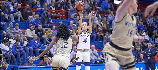 KU senior Mariane De Carvalho (4) shoots a 3-pointer over Wofford's Jamari Mcdavid (12) during KU's nonconference finale Monday night at Allen Fieldhouse on Dec. 30, 2019.