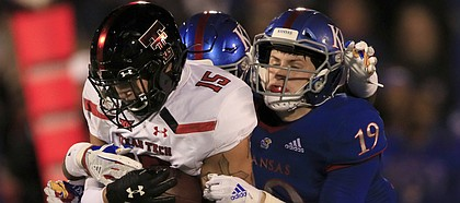 Texas Tech tight end Travis Koontz (15) is tackled by Kansas linebacker Gavin Potter (19) during the first half of an NCAA college football game in Lawrence, Kan., Saturday, Oct. 26, 2019. (AP Photo/Orlin Wagner)