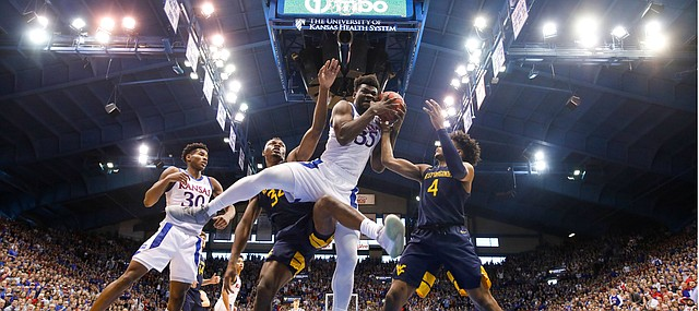 Kansas center Udoka Azubuike (35) gets tangled with West Virginia forward Oscar Tshiebwe (34) and West Virginia guard Miles McBride (4) for a rebound during the first half, Saturday, Jan. 4, 2020 at Allen Fieldhouse.