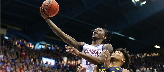 Kansas guard Marcus Garrett (0) gets in for a bucket past West Virginia guard Miles McBride (4) during the second half, Saturday, Jan. 4, 2020 at Allen Fieldhouse.
