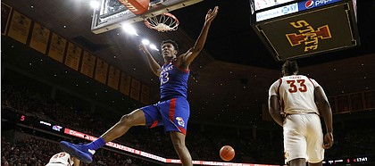 Kansas forward David McCormack reacts after dunking over Iowa State forward Solomon Young, right, during the first half of an NCAA college basketball game Wednesday, Jan. 8, 2020, in Ames, Iowa. (AP Photo/Charlie Neibergall)